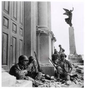 Soldati americani a Troina, di fronte all'entrata della cattedrale della Maria SS Annunziata, dopo il 6 agosto 1943 Fotografato da Robert Capa © International Center of Photography/Magnum  – Collezione del Museo Nazionale Ungherese American soldiers near the entrance of the Maria SS Annunziata Cathedral, Troina, after 6 August 1943 Photograph by Robert Capa © International Center of Photography/Magnum – Collection of the Hungarian National Museum
